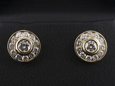 18kt Yellow Gold Rub Over and Channel Set Earrings with 2 x 0.20ct Round Brilliant Diamonds and 0.66ct in Surround.