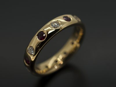 Round Brilliant Cut Diamond 0.44ct (7) & Round Brilliant Cut Rubies 0.53ct (7) Secret Set in 18kt Yellow Gold In an Eternity Ring Design