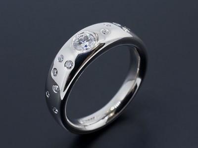 Palladium Halo Band Diamond Ring with Round Brilliants Secret Set into Band.