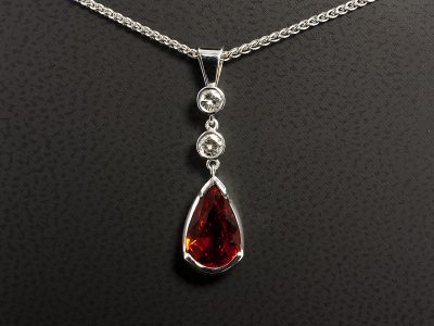 Blood Orange Pear Shape Sapphire 2.83ct with Two Round Brilliant Cut Diamonds Set in 18kt WG in a Rub Over Set Design
