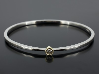 Palladium Bangle with Round Brilliant 0.30ct F Colour VS1 Clarity in an 18kt Yellow Gold Rub Over Setting.