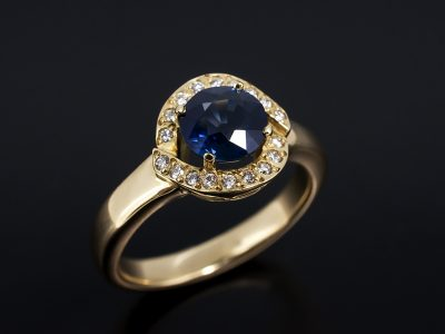 Round Brilliant Cut Sapphire 1.61ct with Round Brilliant Cut Diamonds 0.09ct Set in 18kt Yellow Gold In a Halo Design