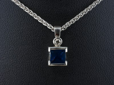 Pendant with Princess Cut Sapphire 1.15ct and Round Brilliant Cut Diamond 0.04ct F Colour VS Clarity Min in 9kt White Gold Settings with Spiga Chain.