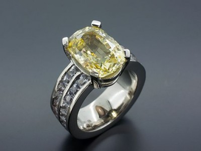 Oval Yellow Sapphire 7.47ct with 4.77ct of Step Cut White Sapphires in an 18kt White Gold Setting with Channel Set Band.