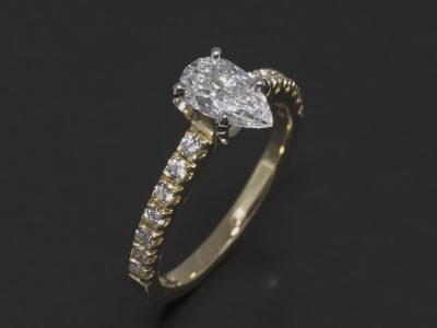 Pear Shape Diamond, 0.71ct, E Colour, VS1 Clarity Four Claw Set in Platinum with a 18kt Yellow Gold Round Brilliant Cut 0.34ct (14) Pavé Set Shoulder