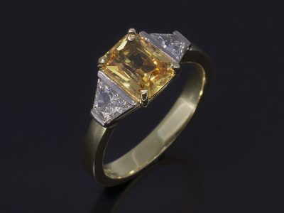 Radient Cut Yellow Sapphire, 1.82ct with Step Cut Trapeziums 0.55ct (2) in a 18kt Yellow & White Gold Trilogy Design