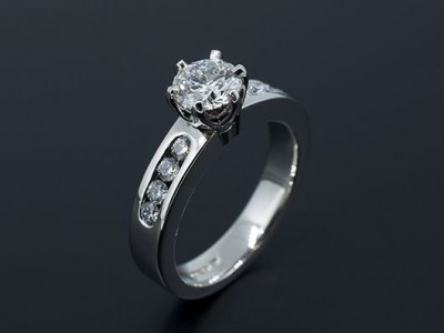 Round Brilliant 0.70ct F Colour SI1 Clarity Triple Excellent in a 6 Claw Platinum setting with Channel Set Side Diamonds.