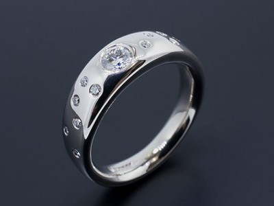 Palladium Halo Band Diamond Ring with Round Brilliants Secret Set into Band.