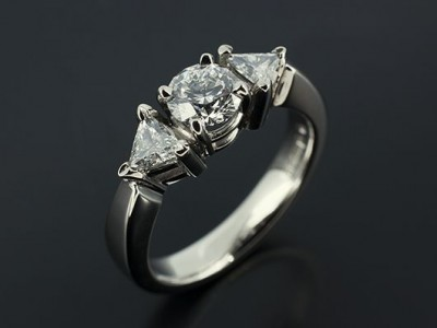 Round Brilliant 0.51ct E Colour SI1 Clarity with 0.23ct Total Trilliant Cut Diamonds in a Palladium Trilogy Setting.