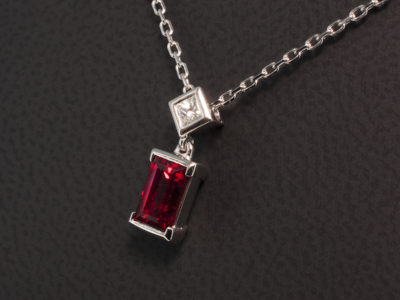 Baguette Cut Blood Orange Sapphire 1.70ct with a Princess Cut Diamond 0.13ct F VS in a 9kt White Gold Part and Full Rub Over Pendant Design.
