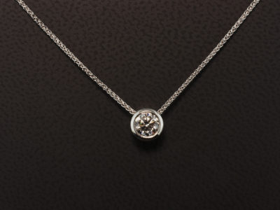9kt White Gold Rub Over Set Pendant with Passing Through Chain Design. Round Brilliant Cut Diamond 0.59ct E Colour, VS1 Clarity Triple Excellent Grade.
