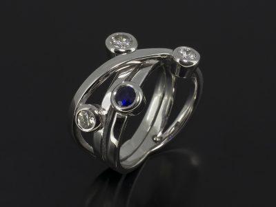 Round Brilliant Cut Diamonds, 0.49ct (3) & Round Brilliant Cut Sapphire Rub-over Set in 9kt White Gold in a Satellite Design