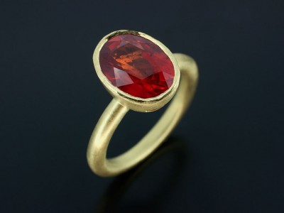 Blood Orange Sapphire 2.97ct in an 18kt Green Gold Rub Over Setting with Halo Shaped Band