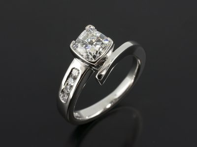 Cushion Cut Diamond, 1.01ct, E Colour, SI1 Clarity, Excellent Polish, Very Good Symmetry in a Platinum Part Rub-over Setting with a Round Brilliant Cut Diamond 0.12ct (4) Channel Set Twist Shoulder