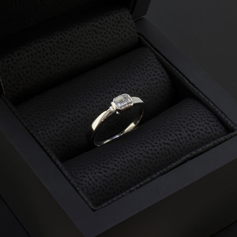 18kt white gold rub over set engagement ring, emerald cut diamond white gold ring, horizontal rub over set diamond ring, F colour diamond ring Glasgow, engagement ring designed and made in Scotland