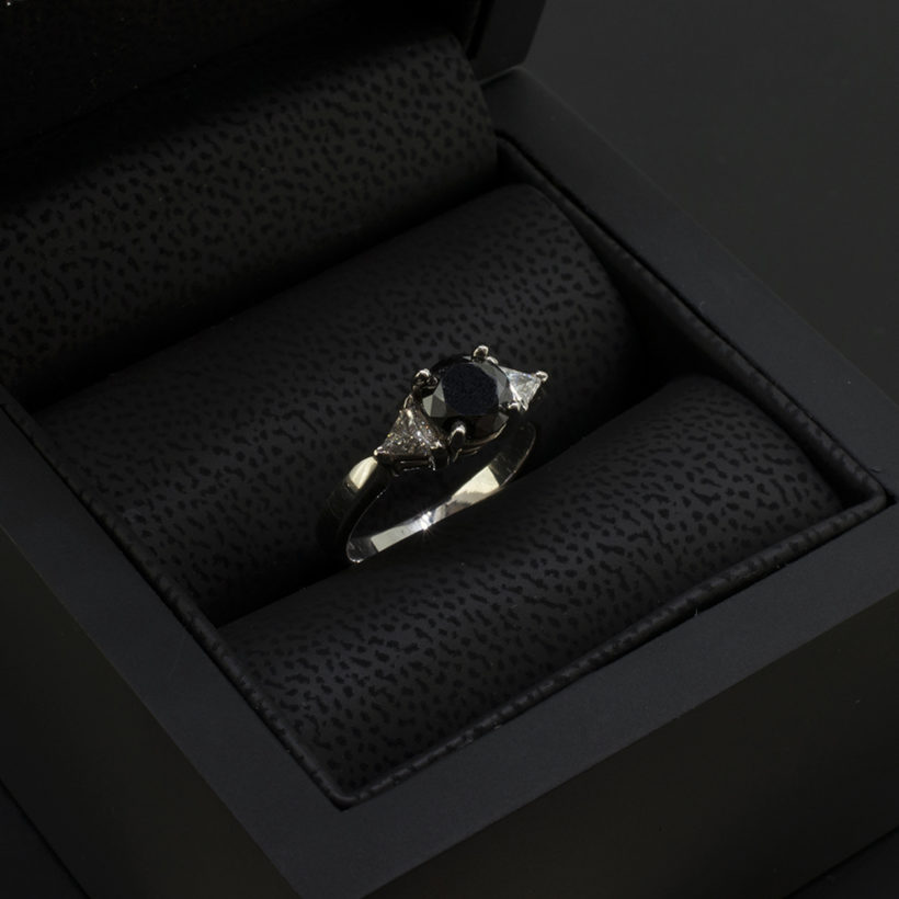 black diamond trilliant shoulder engagement ring, round black diamond ring with side diamonds, trilogy diamond engagement ring