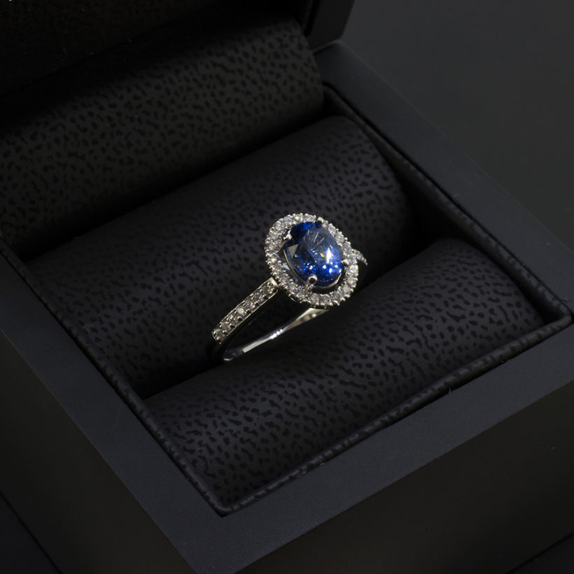 art deco style sapphire halo ring, oval cut sapphire claw set in platinum ring, halo ring with sapphire and diamonds, vintage style engagement ring with claw set sapphire