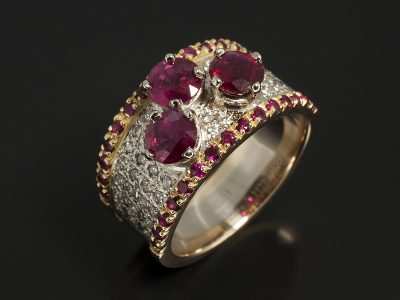 18kt White Gold Claw Set Round Brilliant Cut Rubies 1.94ct (3) with 18kt Yellow and White Gold Pave Set Round Brilliant Cut Diamonds 0.42ct (42) and Round Brilliant Cut Rubies 0.63ct (30) in a Dress Ring Design