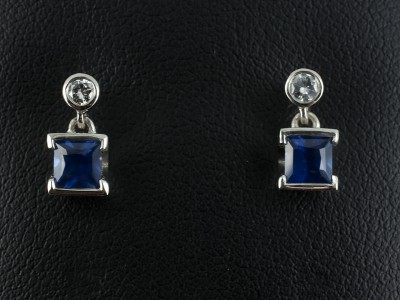 Earrings with Princess Cut Sapphires 0.88ct Total and Round Brilliant Cut Diamonds 0.12ct F Colour SI Clarity Min in 9kt White Gold Settings.