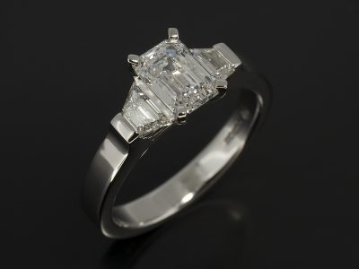 Emerald Cut Diamond 1.01ct D Colour SI1 Clarity Claw Set in Platinum with Step Cut Trapeziums 0.36ct (2) in a Trilogy Design