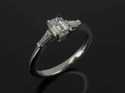 Emerald Cut 0.50ct H Colour SI1 Clarity with Tapered Baguette Cuts 0.20ct in a Palladium Claw Set Trilogy Design.