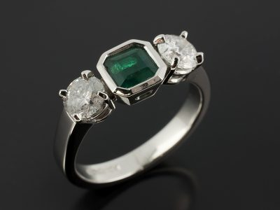 Emerald 0.65ct and Round Brilliant Cut Side Diamonds 0.52ct and 0.54ct F SI in a Platinum 4 Claw and Rub Over Set Design.