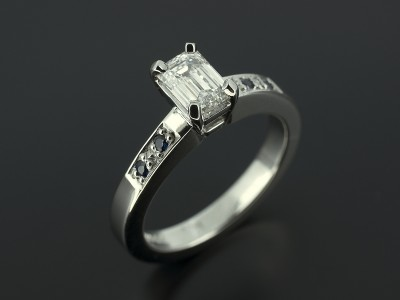 Emerald Cut 0.70ct D Colour VS1 Clarity in an Offset Palladium 4 Claw Setting with Pavé Set Round Brilliant Sapphires.
