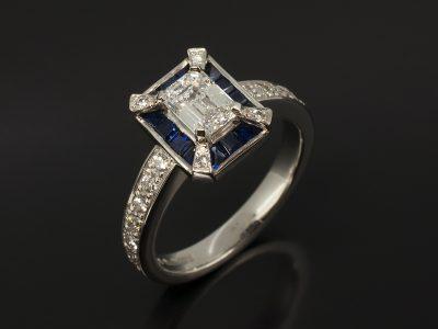 Emerald Cut Diamond, 0.79ct, D Colour, VS1 Clarity, Four Claw Set In Platinum with Channel Set Step Cut Sapphire Halo and Pavé Set Round Brilliant Cut Diamond 0.30ct (18) Shoulder