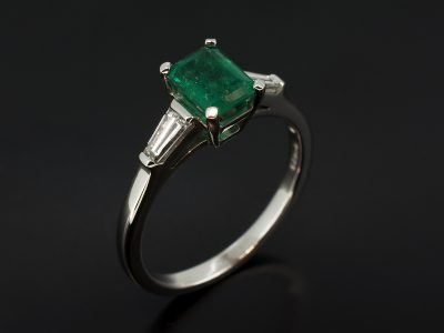 Emerald Cut Emerald, 0.79ct Claw Set in 18kt White Gold with Tapered Baguette Diamond Sides 0.18ct (2) in a Trilogy Design