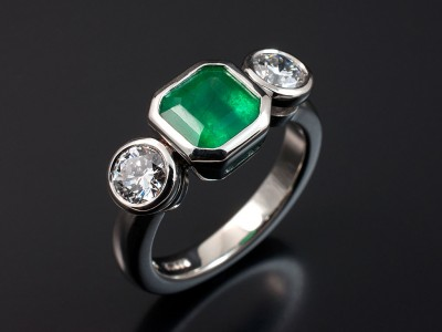 Emerald Cut Emerald 1.40ct with 2 x 0.40ct G SI1 Round Brilliant Diamonds in an 18kt White Gold Rub Over Setting