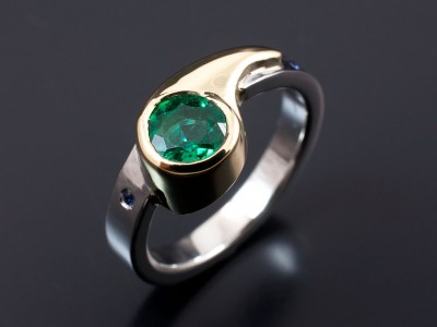 Round Emerald 0.81ct in a Hand Made 18kt Yellow Gold and Palladium Setting with 2 x Round Sapphires Secret Set into Band.