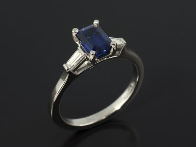 Emerald Cut Sapphire 1.36ct with Tapered Baguette Cut Diamonds 0.23ct F VS in a Platinum Claw Set Design.