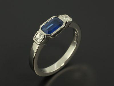 Emerald Cut Sapphire 0.63ct and Asscher Cuts Diamonds 0.18ct in a Palladium Trilogy Rub Over Set Design.