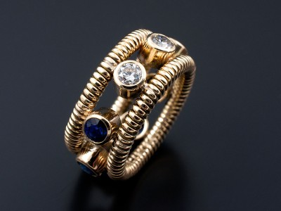 Eternity Ring Wedding Ring with Round Sapphires and Round Brilliant Diamonds set in 9kt Yellow Gold Rub Over Settings with Coiled Bands.