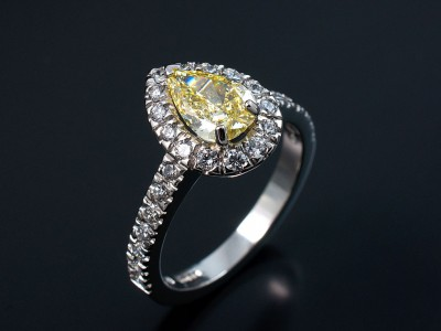 Fancy Intense Yellow 0.74ct VS1 Clarity Pear Cut Diamond in a Platinum Diamond Claw Set Halo Design.