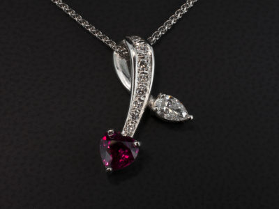 Heart Shaped Ruby 0.94ct and Pear Shaped Diamond 0.29ct F Colour SI Clarity with Round Brilliant Cut Diamonds 0.12ct Total, Claw and Pavé Set into a Looped Dropped Platinum Pendant Design.