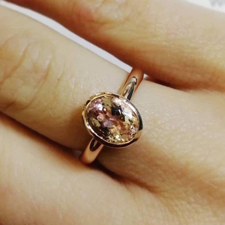 Oval Cut Morganite Ring 1.60ct in a 9kt Rose Gold Rub Over Set Design with Halo Shaped Band.