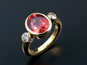 Oval 4.2ct Blood Orange Sapphire with 2 x 0.20ct F VS Round Brilliants in 18kt Yellow Gold Rub Over Settings