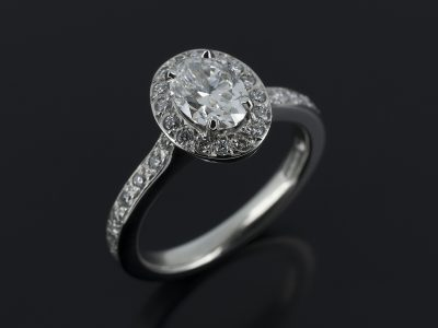 Oval Cut Diamond, 0.70ct, F Colour, SI1 Clarity Four Claw Set in Platinum with a Round Brilliant Cut Diamond, 0.26ct (30), Pavé Set Halo and Shoulder