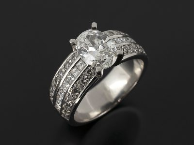 Oval Cut Diamond, 1.05ct Claw Set in Platinum with a Round Brilliant Cut Diamond, 0.32ct (28) Pavé Set and Princess Cut Diamond 0.38ct (16) Channel Set Shoulder