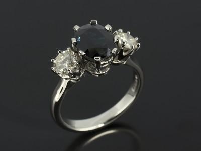 Oval Dark Sapphire 2.26ct with 2 x Round Brilliant Diamonds 0.83ct Total in Palladium Trilogy Setting.