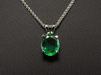 18kt White Gold Claw Set Pendant with Double Bale. Oval Cut Zambian Emerald 1.56ct.