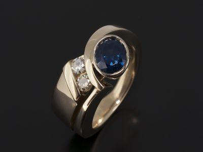 Oval Cut Sapphire, 1.61ct Rub-over Set in 18kt Yellow Gold with Tension Set Round Brilliant Cut Diamonds. 0.23ct (2) in a Twist Design