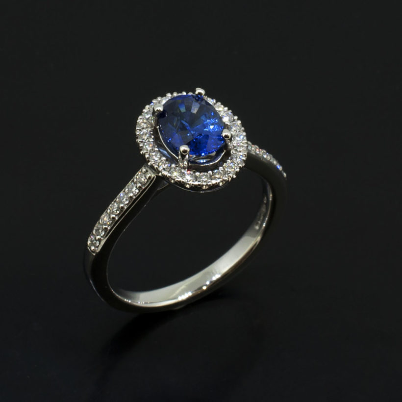 Oval Cut Sapphire 1.25ct with Round Brilliant Cut Diamonds 0.25ct Total in a Platinum Claw Set Halo Design, halo design sapphire and diamond ring, halo design engagement ring, oval cut sapphire ring with pave shoulders, platinum claw set halo ring, fine jewellery designed and made in scotland, 1.25ct sapphire ring, vintage style art deco ring