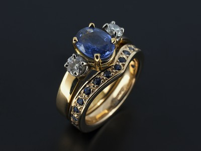 Oval Ceylon Sapphire 1.45ct with 2 x 0.15ct Round Brilliant Diamond Trilogy Design in 18kt Yellow Gold with Matching Pavé Set Sapphire Fitted Wedding Ring.