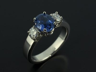 Oval Ceylon Sapphire 1.98ct with 2 x 0.25ct Round Brilliant Diamonds in a Palladium 4 Claw Trilogy Design.