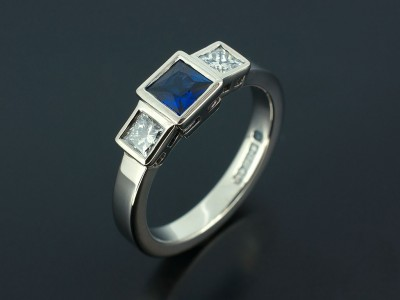 Palladium Trilogy Engagement Ring with Princess Cut Sapphire 0.46ct and Princess Cut Diamonds 0.37ct (2) F Colour VS Clarity Min Set in Rub Over Settings. Copy