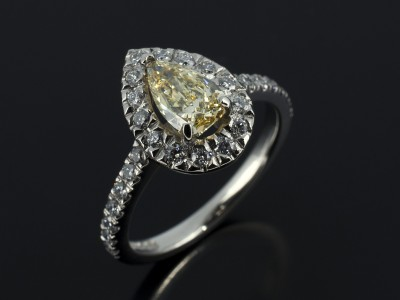 Fancy Yellow 0.65ct Pear Cut Diamond in a Palladium Diamond Set Halo Design.