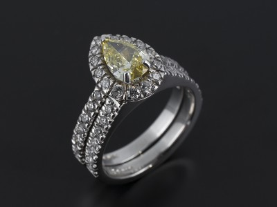 Fancy Intense Yellow 0.74ct VS1 Clarity Pear Cut Diamond in a Platinum Diamond Claw Set Halo Design with Fitted Diamond Claw Set Wedding Ring