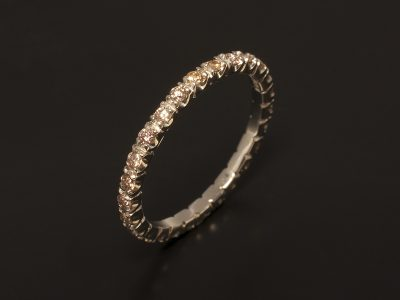Platinum Full Claw Set Eternity Ring with Peach Coloured Diamonds.